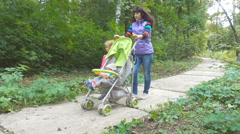 Young mother walking in autumn park with her baby son in a stroller and Littl Stock Footage