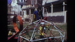 1973: children playing outside in a yard on a jungle gym/dome PHILADEPHIA Stock Footage