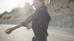 Beautiful skinny girl in shorts running around and jumping on the empty driveway Stock Footage