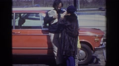 1973: a man, woman and child standing in a parking lot next to a car PHILADEPHIA Stock Footage