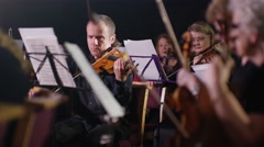 4K Symphony orchestra during a performance with focus on violinists Stock Footage