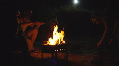People sit at night round a bright bonfire Stock Footage