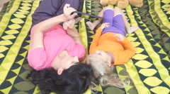 Little daughter and mother using a tablet computer while lying on a bed. Stock Footage