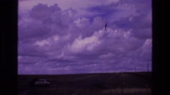 1973: a car is driving off into the horizon which is filled with clouds over Stock Footage