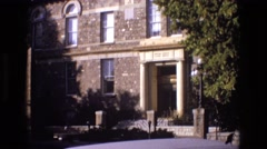 1973: two story building made of brick and stone with concrete columns painted Stock Footage