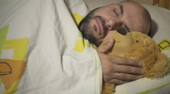 Adult male sleeping and hugging teddy bear. Stock Footage