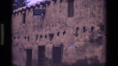 1973: southwestern style rustic building exterior with a blue sign near roof Stock Footage