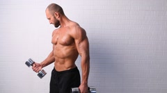 Strong topless man doing exercise with dumbbells Stock Footage