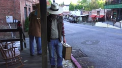 Old gold mining town, cowboy holding old suitcase Stock Footage