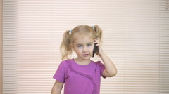 Little girl talking on a cell phone.The child learns by telephone the good ne Stock Footage