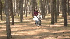 Boy running with a paper airplane and it catches up with his mom Stock Footage