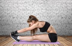 Young woman with athletic body doing stretching workout in training dress, focus Kuvituskuvat