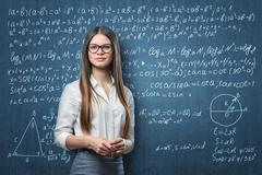 Young businesswoman standing on the background of blackboard with mathematical Stock Photos