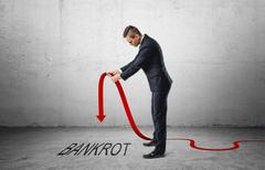 Businessman holding red line graph with downturned arrow which is pointing to Stock Photos