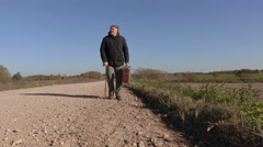 Disabled man with cane and suitcase on the road Stock Footage