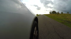 4K Unique angle showing a car speeding along a country lane Stock Footage