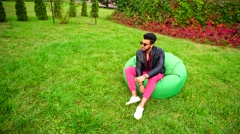 Arab Guy Musingly Looks Aside, Rest and Sitting in Chair in Green Garden. Stock Footage