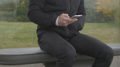 Close-up of a man using smart phone at a bus stop Stock Footage