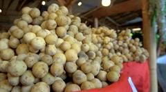 Choosing longan at fruit stall Stock Footage