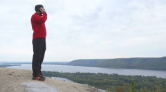 Tourist man He is standing in the mountains, and talking on the phone .  hiki Stock Footage
