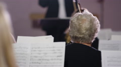 4K View from behind orchestra violinists with conductor in background Stock Footage