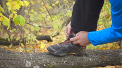 Man runner tying her shoes on a fallen tree in the autumn forest. Slow Motion Stock Footage