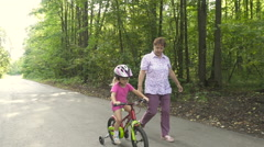 Grandmother learns to ride a bike little granddaughter. Happy child riding a Stock Footage