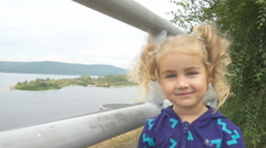 Cute Little Girl With Pigtails Smiles Looks  At Camera. Windy Day on the back Stock Footage