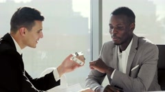 Real-estate black agent with man signing contract in modern white european Stock Footage