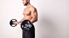 Topless bodybuilder working out with weights Stock Footage