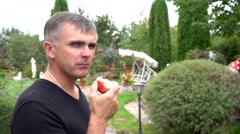 Attractive man eating red apple in garden. Smiling man bitten a healthy apple Stock Footage