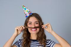 Woman in celebration cap making moustache of her hair Stock Photos