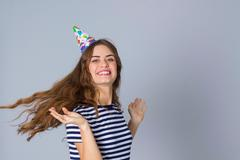 Woman in celebration cap whirling Stock Photos