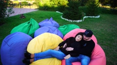 Young Boyfriend and Girlfriend Sitting and Talk in Multicolored Armchairs and Stock Footage