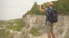 Tourist man with smartphone in mountain . men with backpack in the woods. hik Stock Footage