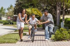 African American Family WIth Boy Riding Bike & Happy Parents Stock Photos