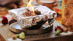 Wood burns in the bowl on table during pre-wedding Hindu ceremony Stock Footage