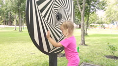 Little girl plays with Hypnotic spiral tunnel circle looping in the park in s Stock Footage