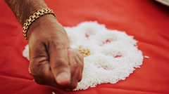 Indian man covers rice on the red cloth with wheat Stock Footage
