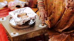 Hindu woman puts rice over the nuts during pre-wedding ceremony Stock Footage