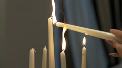 Close-up of lighting a candle against a black background Stock Footage
