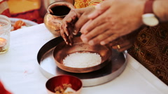 Woman with hands in mehendi puts rice in bronze plate Stock Footage