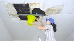 Young Woman Collecting Water In Bucket From Ceiling. Ceiling panels damaged h Stock Footage
