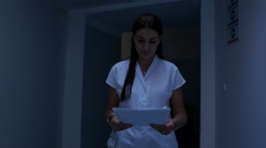 Doctor looks at a patient's notes as she walk down a hospital corridor Stock Footage