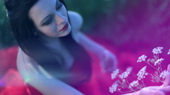 Fairy girl sitting in a field in a red dress among the flowers at sunset. Stock Footage
