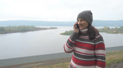 Young woman talking on the phone outdoors on background of the river and moun Stock Footage