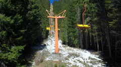 Aerial ski lift with yellow painted wooden seats and iron breakover towers Stock Footage