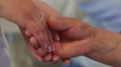 Close up of a hand of a young nurse or doctor holding an old hand of a patient Stock Footage
