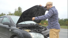 Men closed  the car hood and visually inspects examines the motor engine. The Stock Footage