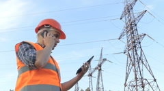 Electrical engineer working. Talking on the phone and working on the tablet.C Stock Footage